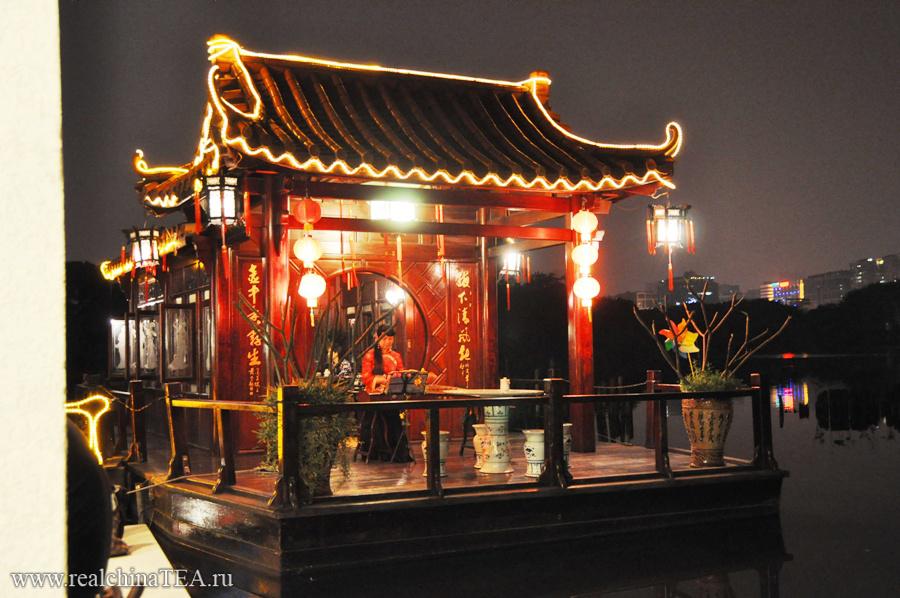 Один из чайных залов расположен прямо на воде. Там девушка играет на национальном музыкальном инструменте.