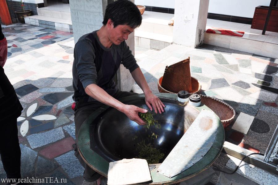 Это чайный мастер. Он обрабатывает чайный лист. Сейчас он засыпает свежие листочки в свой котел. Через тридцать минут манипуляций этот лист превратится в великолепный Лунцзинь. Его можно будет тут же заварить и выпить.