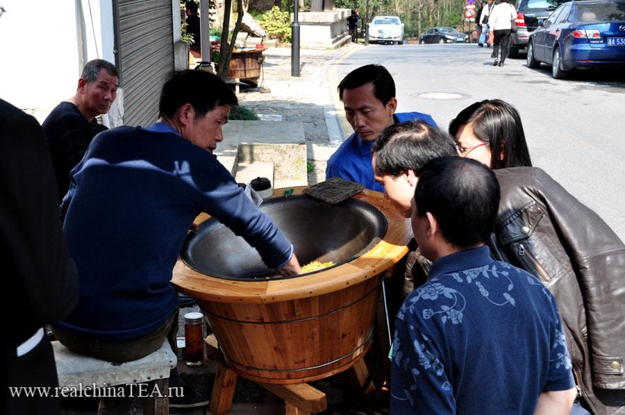 Чайный мастер и любопытные туристы в одной из чайных деревушек возле города Ханчжоу.