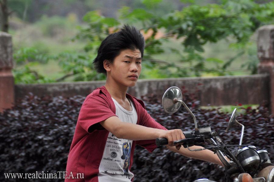 Сын чайного фермера на мотоцикле на платнациях.