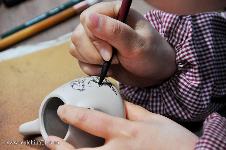 Все, абсолютно все в исинских чайниках делается вручную. Даже рисунок. Мастер сначала наносит изображение специальным карандашом. Затем оно покрывается термостойким прозрачным лаком и чайник отправляется в печь.