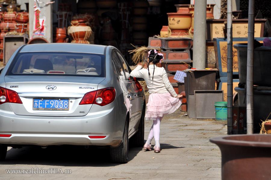 Девятилетняя дочка директора фабрики модничает перед зеркалом папиной машины. )))