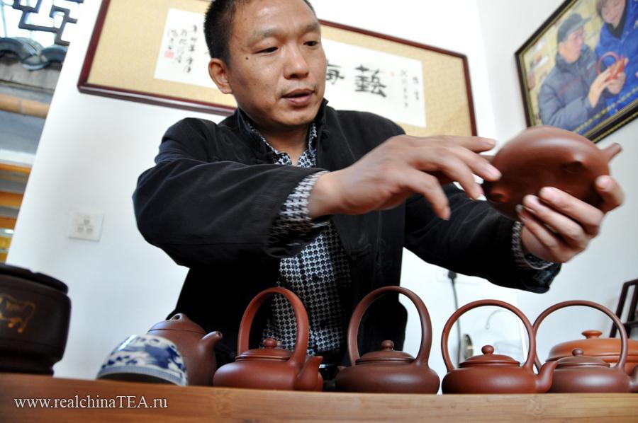 Мастер Лин рассказывает про свои чайники. Они уже изготовлены, но еще не обожжены. Завтра их ждет печь. После чего они будут выставлены на продажу. Обычно мастер готовит чайники небольшими партиями по 10-12 шутк.